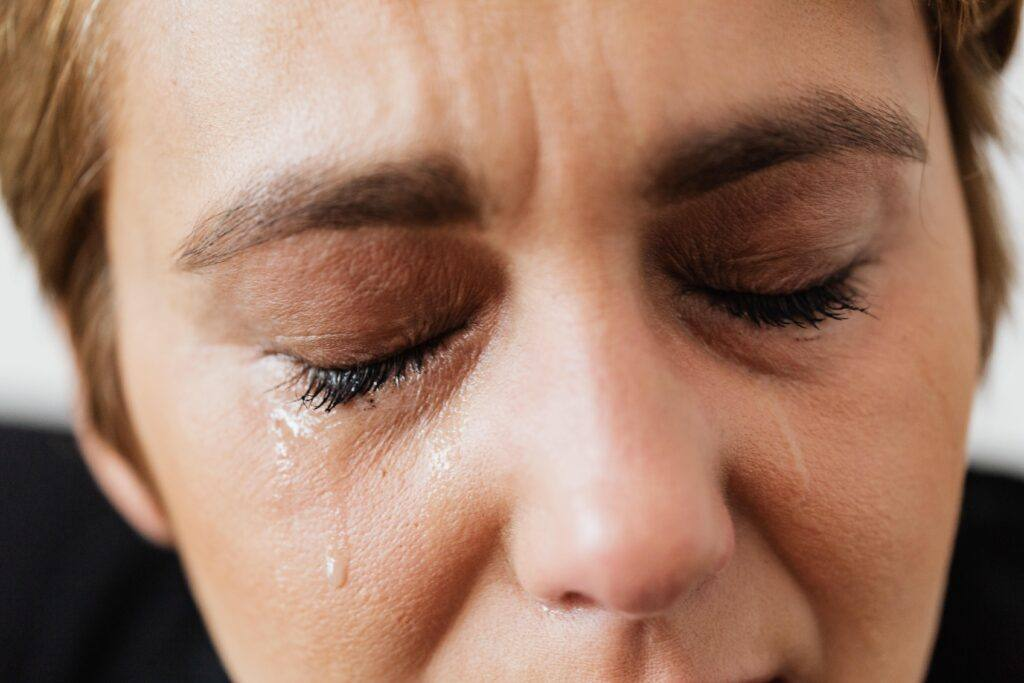 woman grieving, crying with tears